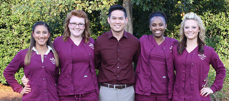 Dr. Do smiling outside with his dental team