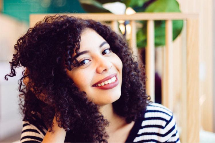 girl with dark curly hair smiling broadly with porcelain veneers