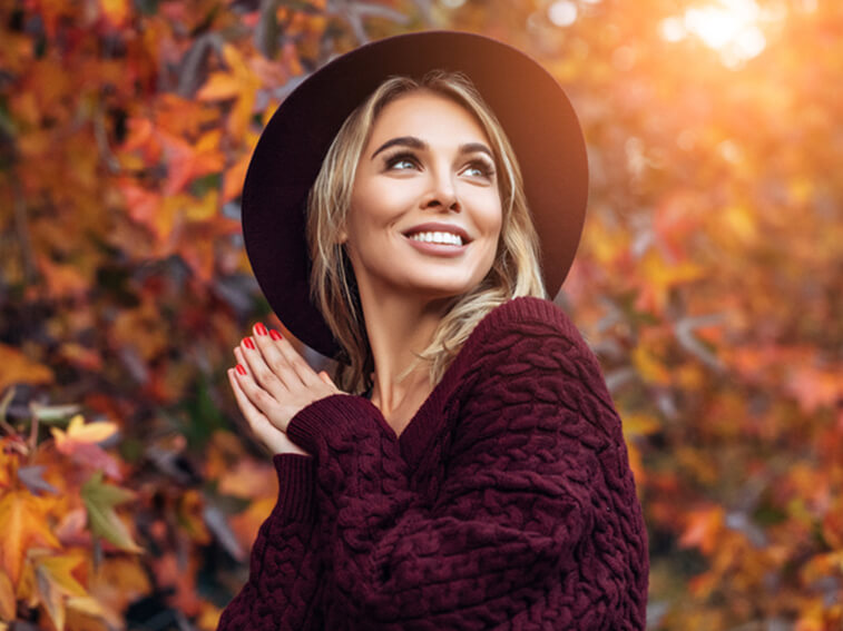 Woman in hat and burgandy sweater smiling
