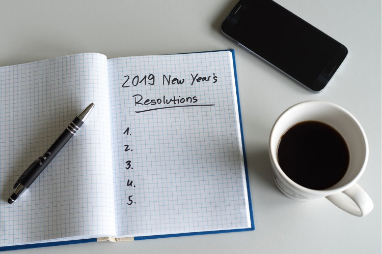 2019 notebook for new years resolutions, a pen, cup of coffee and phone