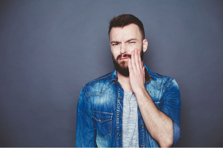 bearded man wearing a denim jacket holds the side of his mouth where a filling has fallen out