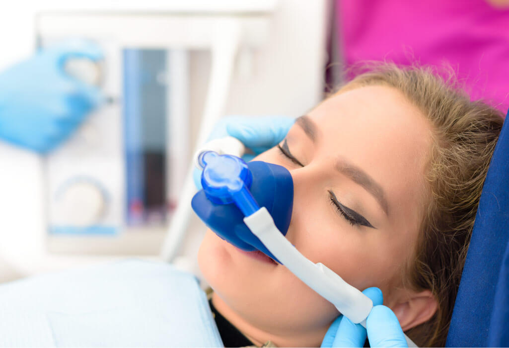 Woman relaxes with a nitrous oxide mask over her nose in the dental chair at Red Oak Family Dentistry in McKinney, TX