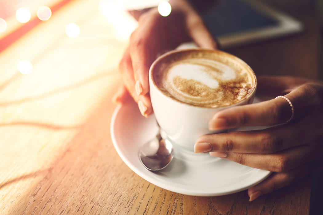 Closeup of woman's hands touching a cup of coffee, a drink that stains teeth